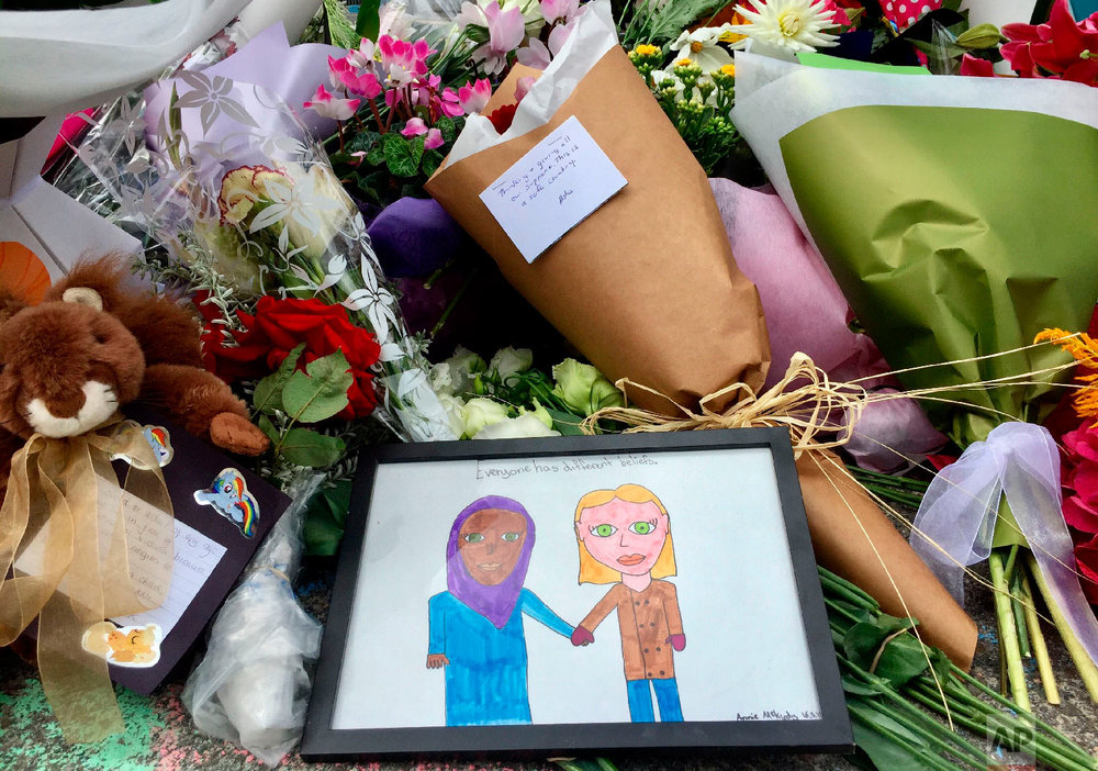 Flowers and tributes are placed outside the Islamic Centre in Kilbirnie, Wellington, New Zealand, Saturday, March 16, 2019. (New Zealand Herald via AP)