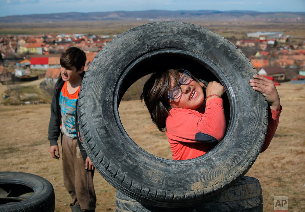 A little girl struggles to lift a tire during a ritual marking the upcoming Clean Monday, the beginning of the Great Lent, 40 days ahead of Orthodox Easter, on the hills surrounding the village of Poplaca, in central Romania's Transylvania region, Sunday, March 10, 2019. (AP Photo/Vadim Ghirda)