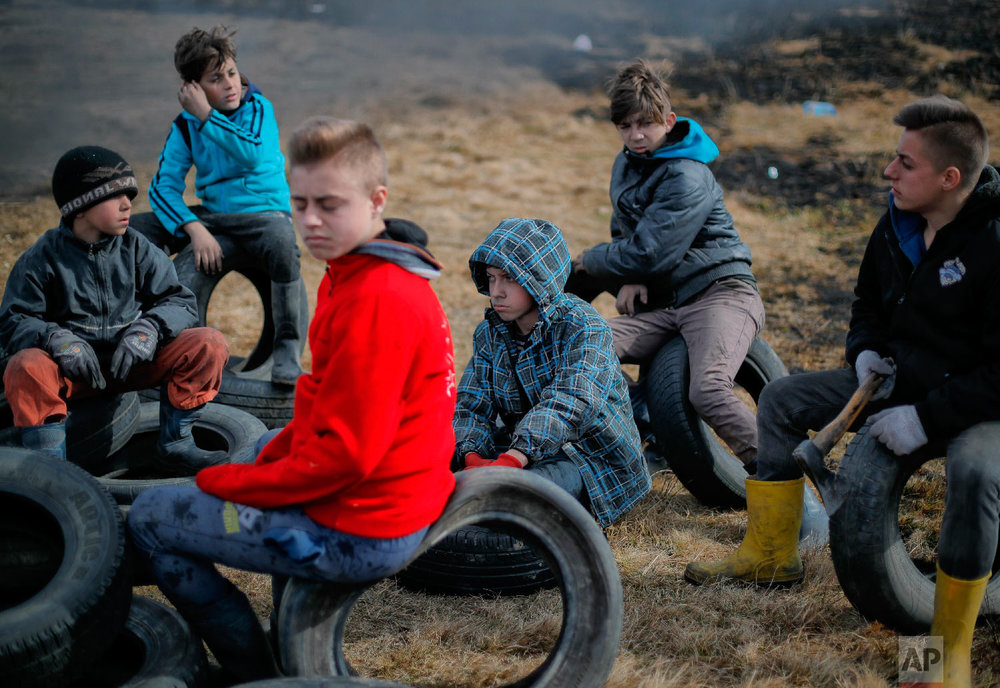 Children sit on tires during a ritual marking the upcoming Clean Monday, the beginning of the Great Lent, 40 days ahead of Orthodox Easter, on the hills surrounding the village of Poplaca, in central Romania's Transylvania region, Sunday, March 10, 2019. (AP Photo/Vadim Ghirda)