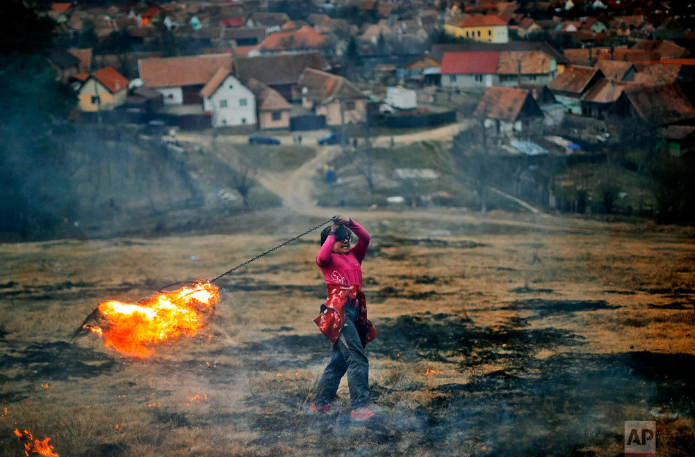 A little girl spins a burning tire on a metal chain during a ritual marking the upcoming Clean Monday, the beginning of the Great Lent, 40 days ahead of Orthodox Easter, on the hills surrounding the village of Poplaca, in central Romania's Transylvania region, Sunday, March 10, 2019. (AP Photo/Vadim Ghirda)