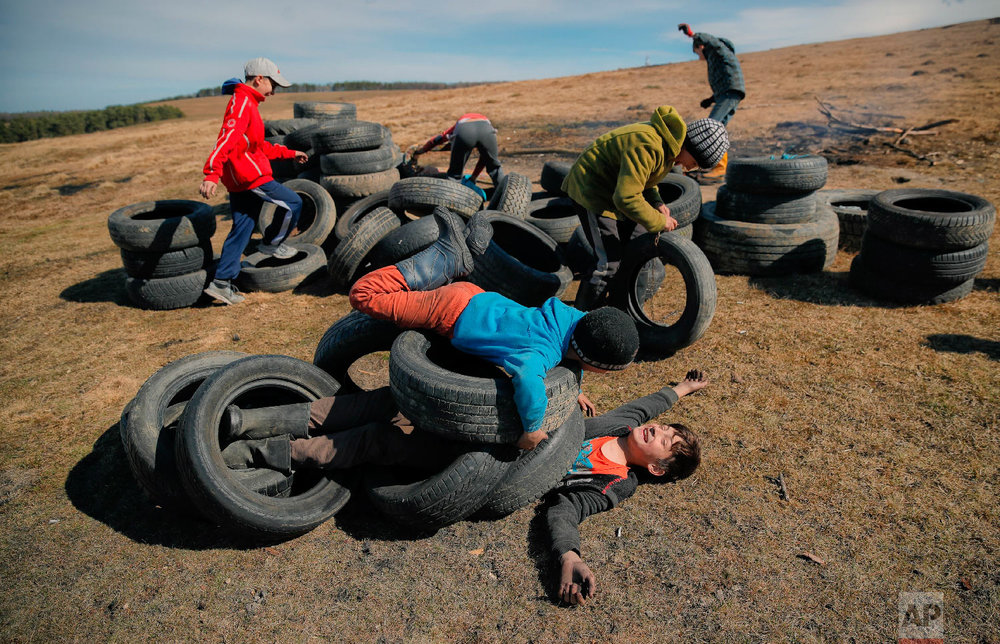 Children play with used tires before a ritual marking the upcoming Clean Monday, the beginning of the Great Lent, 40 days ahead of Orthodox Easter, on the hills surrounding the village of Poplaca, in central Romania's Transylvania region, Sunday, March 10, 2019. (AP Photo/Vadim Ghirda)