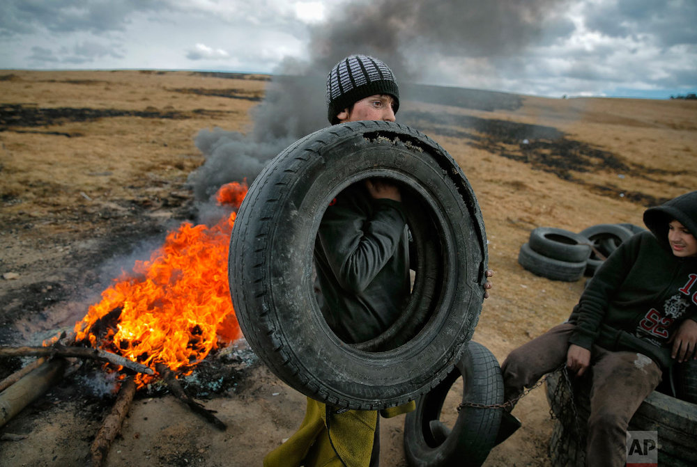 A boy handle tires during a ritual marking the upcoming Clean Monday, the beginning of the Great Lent, 40 days ahead of Orthodox Easter, on the hills surrounding the village of Poplaca, in central Romania's Transylvania region, Sunday, March 10, 2019. (AP Photo/Vadim Ghirda)
