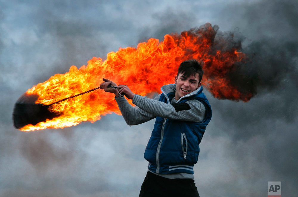 A young man spins a burning tire on a metal chain, during a ritual marking the upcoming Clean Monday, the beginning of the Great Lent, 40 days ahead of Orthodox Easter, on the hills surrounding the village of Poplaca, in central Romania's Transylvania region, Sunday, March 10, 2019. (AP Photo/Vadim Ghirda)