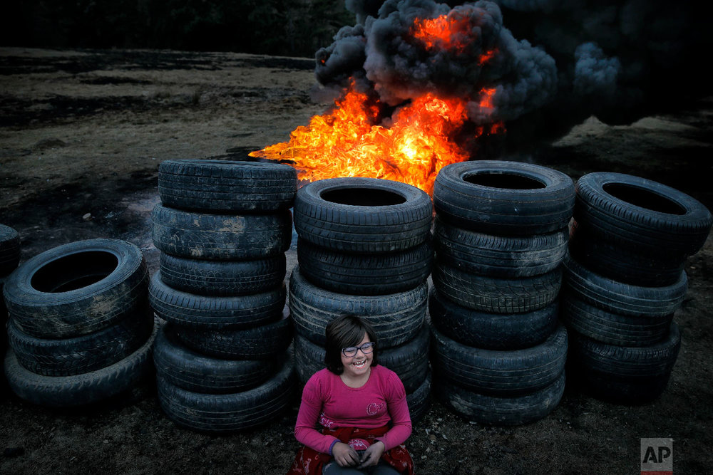 A little girl rests leaning against used tires during a ritual marking the upcoming Clean Monday, the beginning of the Great Lent, 40 days ahead of Orthodox Easter, on the hills surrounding the village of Poplaca, in central Romania's Transylvania region, Sunday, March 10, 2019. (AP Photo/Vadim Ghirda)