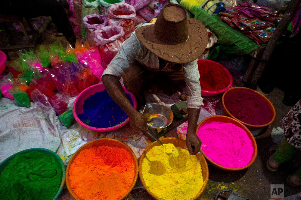 An Indian street vendor sells colored powder a day ahead of Holi, March 20, 2019. (AP Photo/Anupam Nath)