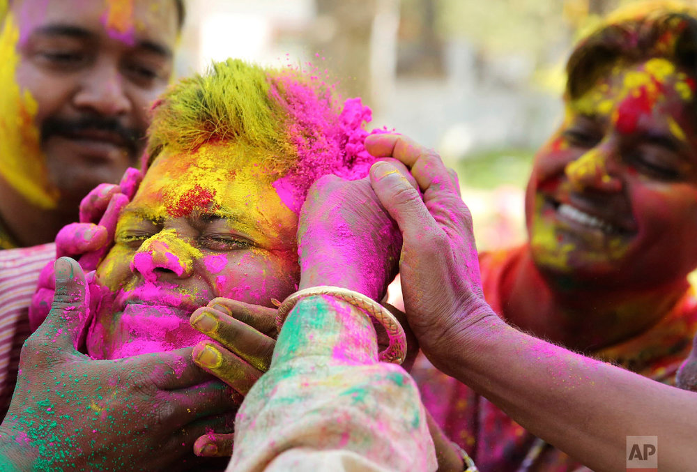An Indian man has colored powder smeared on his face during celebrations marking Holi, the Hindu festival of colors, in Allahabad, India, Wednesday, March 20, 2019. (AP Photo/Rajesh Kumar Singh)
