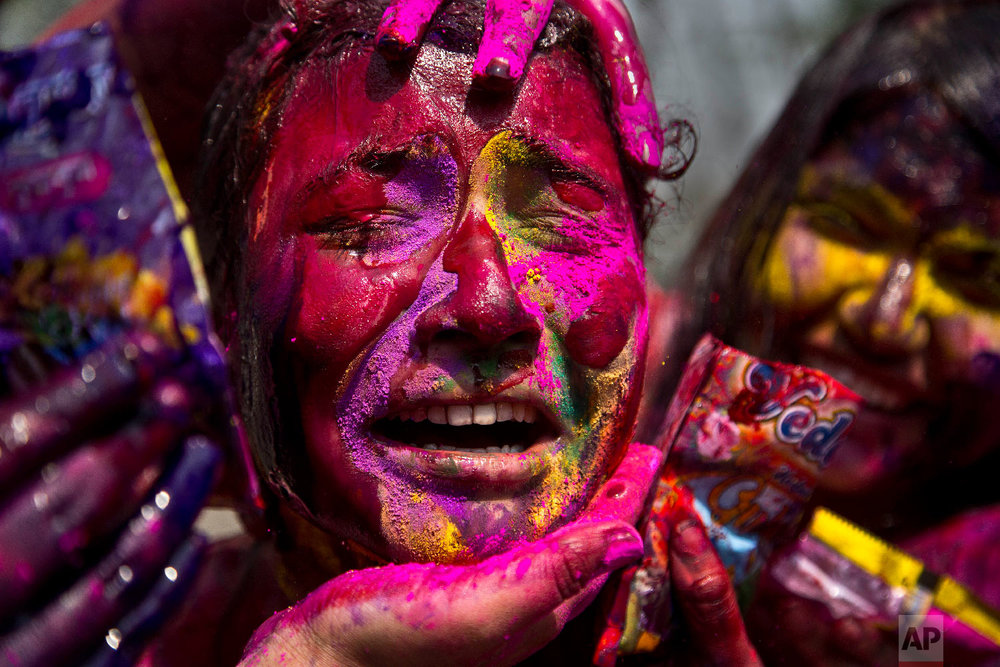 An Indian girl grimaces as her face is smeared with colored powder during celebrations marking Holi, the Hindu festival of colors, in Gauhati, India, Thursday, March 21, 2019. (AP Photo/Anupam Nath)