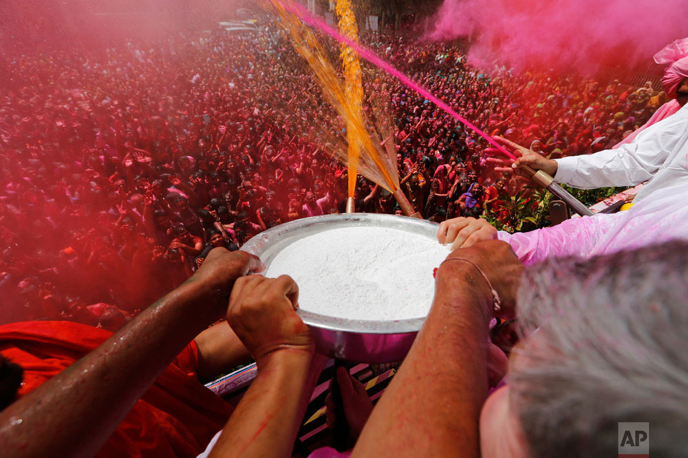 Indian priests spray colored water and powder on devotees during celebrations marking Holi on March 20, 2019. (AP Photo/Ajit Solanki)