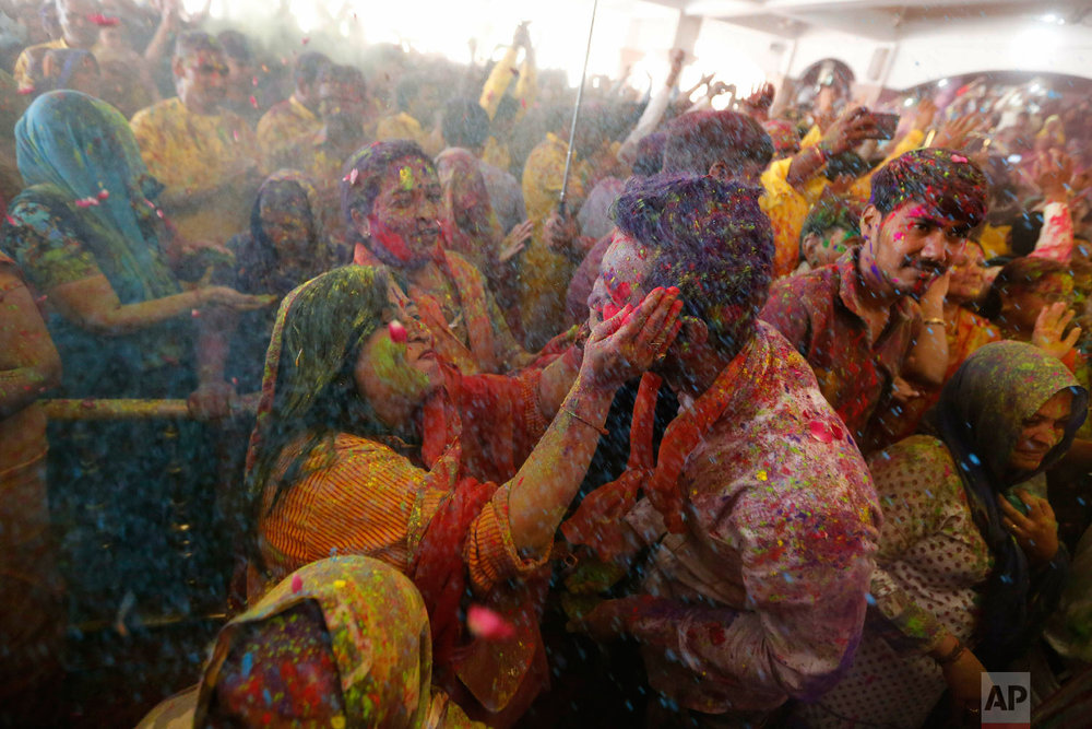 A Indian Hindu devotee applies colored powder to another during Holi festival celebration at the Lord Jagannath temple in Ahmadabad, India, Thursday, March 21, 2019. (AP Photo/Ajit Solanki)