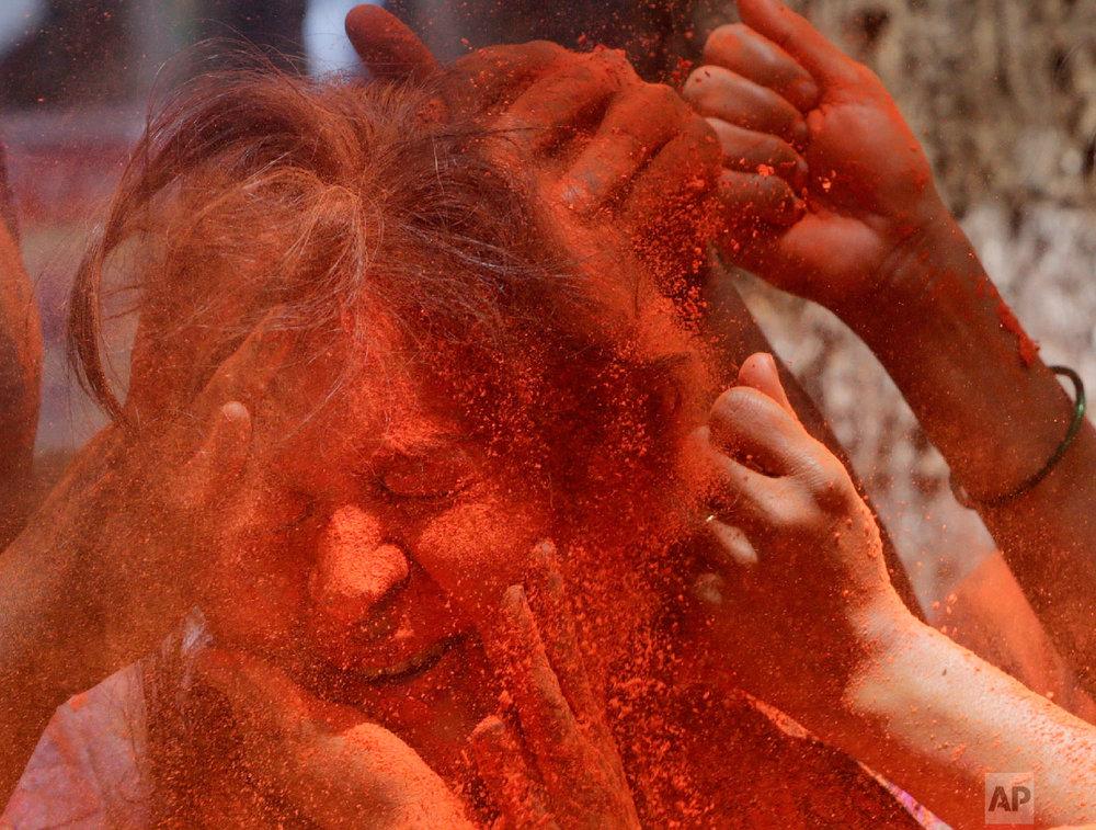 Revelers smear colored powder on a woman during celebrations marking Holi, the Hindu festival of colors, in Mumbai, India, March 21, 2019. (AP Photo/Rajanish Kakade)