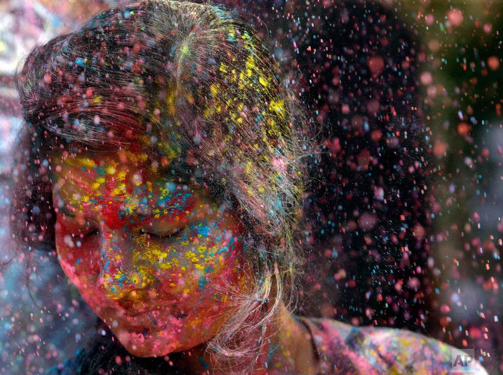 Revelers throw colored powder on a woman during celebrations marking Holi, the Hindu festival of colors, in Mumbai, India, Thursday, March 21, 2019. (AP Photo/Rajanish Kakade)