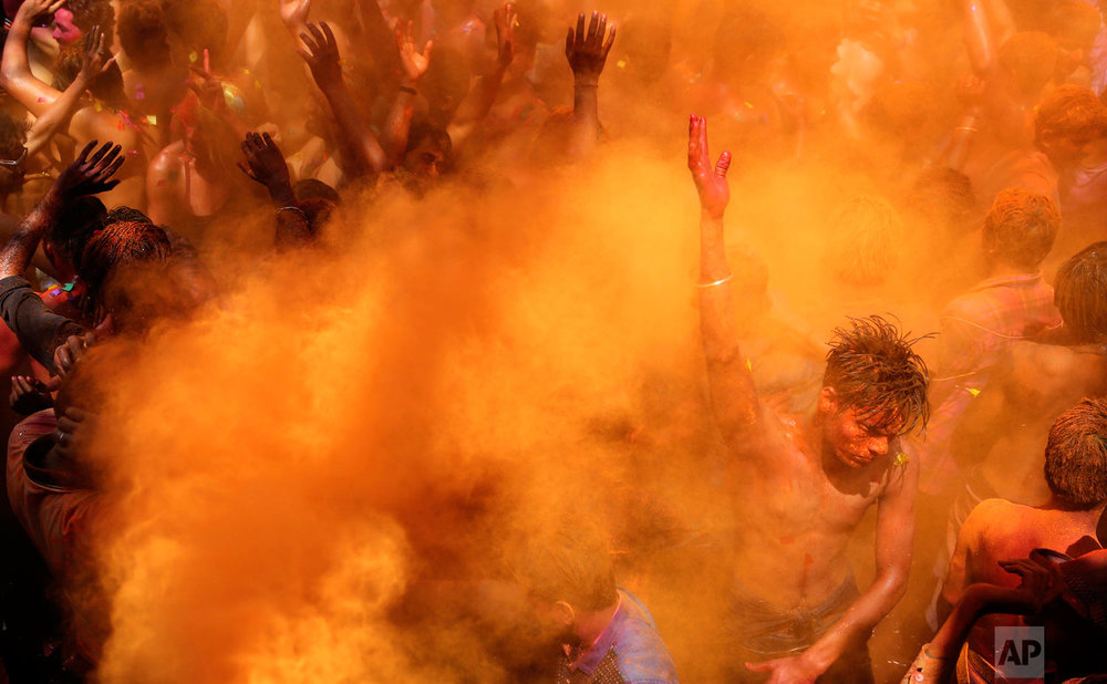 Indian revelers dance as color is sprayed on them during celebrations to mark Holi, the Hindu festival of colors, in Prayagraj, India, Friday, March 22, 2019. (AP Photo/ Rajesh Kumar Singh)
