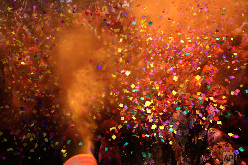Indian revelers dance as colored powder and confetti are showered on them during celebrations to mark Holi, the Hindu festival of colors, in Prayagraj, India, Friday, March 22, 2019. (AP Photo/ Rajesh Kumar Singh)