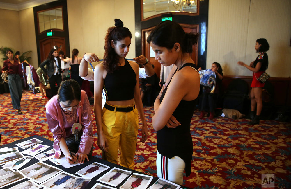 A tailor takes the measurements of a model as a woman scans photographs during a fitting session ahead of the Lotus Makeup India Fashion Week, Monday, March 11, 2019, in New Delhi, India. (AP Photo/Manish Swarup)