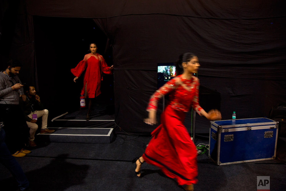 Models rush for a quick change of outfit during the Lotus Makeup India Fashion Week, Wednesday, March 13, 2019, in New Delhi, India. (AP Photo/Manish Swarup)