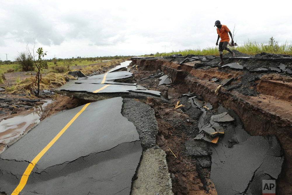 A man walks through a section of a road damaged by Cyclone Idai in Nhamatanda, Mozambique, about 50 kilometers (30 miles) from Beira, on Friday March, 22, 2019. As flood waters began to recede in parts of Mozambique on Friday, fears rose that the death toll could soar as bodies are revealed. (AP Photo/Tsvangirayi Mukwazhi)