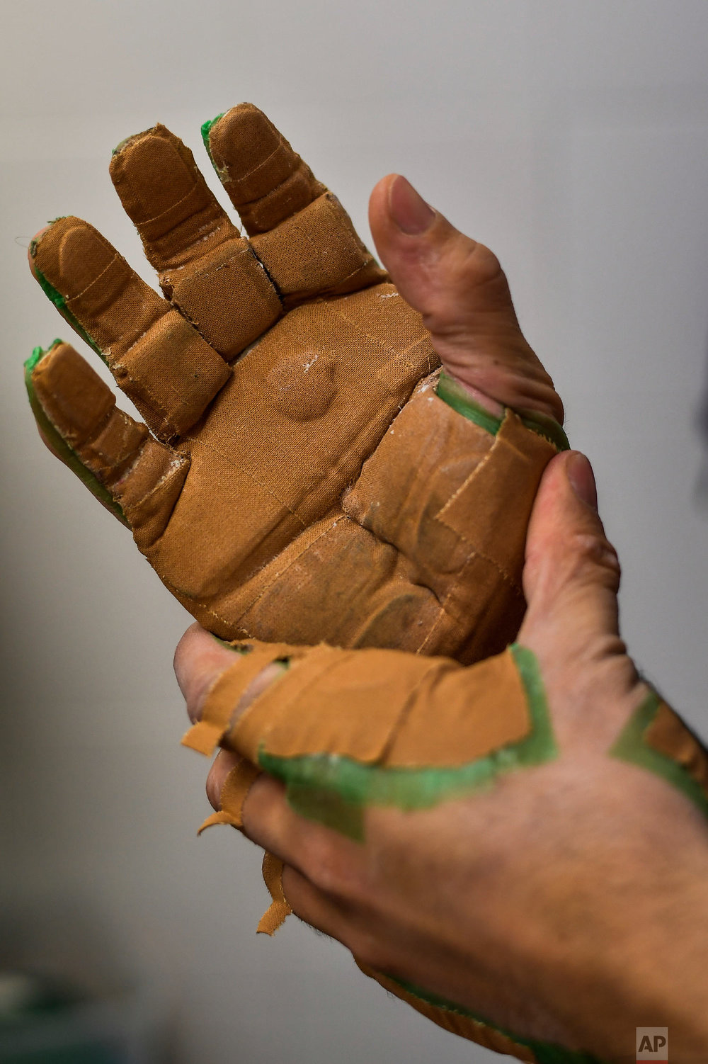 """Victor Esteban, a player of Basque Ball, known as """"pelotari"""", prepares and protects his hands ahead of a training session, in Pamplona, Spain on Feb. 28, 2019. (AP Photo/Alvaro Barrientos)"""