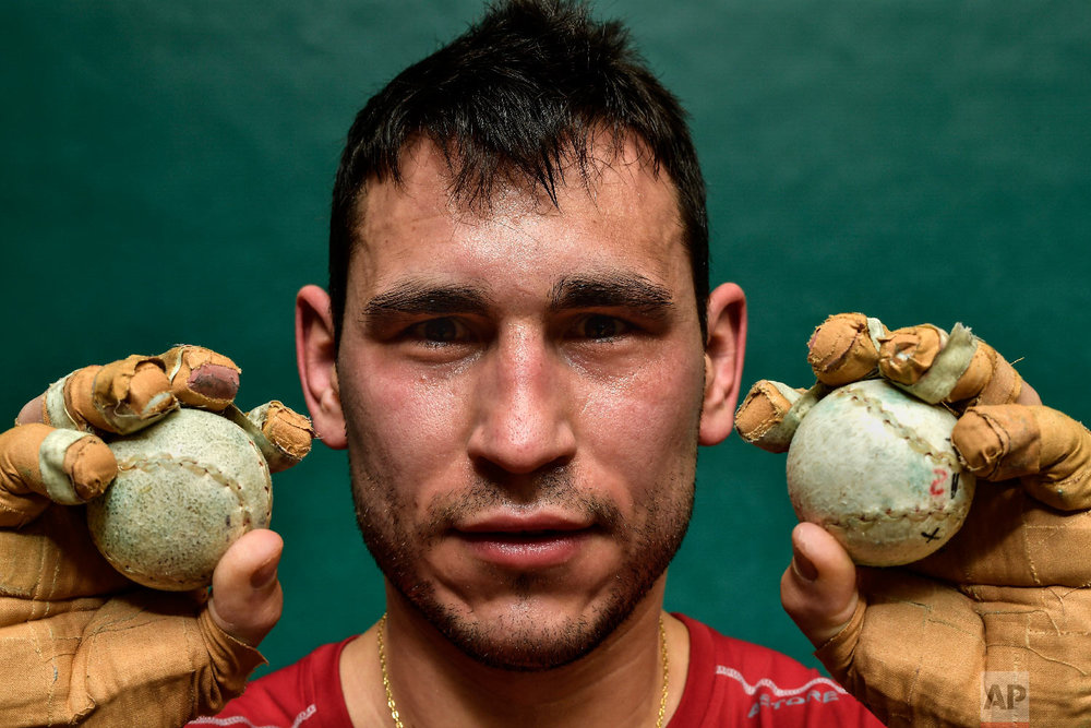 """Diego Iturriaga, 27, a player of Basque Ball known as """"pelotari"""", holds Basque Balls as he poses for a photo at Labrit court or fronton, in Pamplona, northern Spain on March 5, 2019. (AP Photo/Alvaro Barrientos)"""