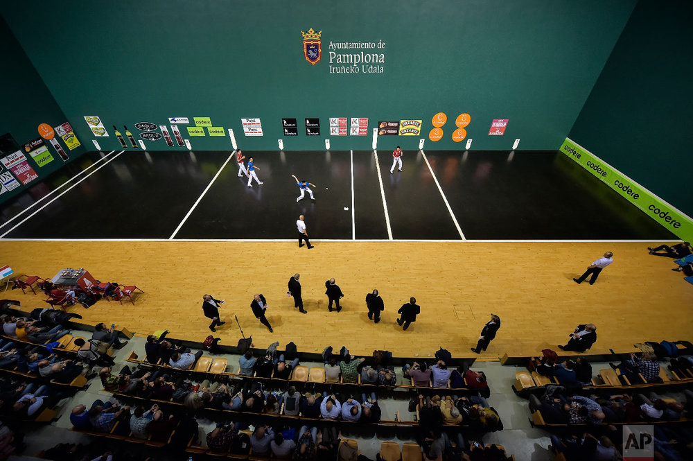 Victor Esteban, center, prepares to hit the ball with his hand during a match at Labrit court or fronton, in Pamplona, northern Spain on March 9, 2019. (AP Photo/Alvaro Barrientos)