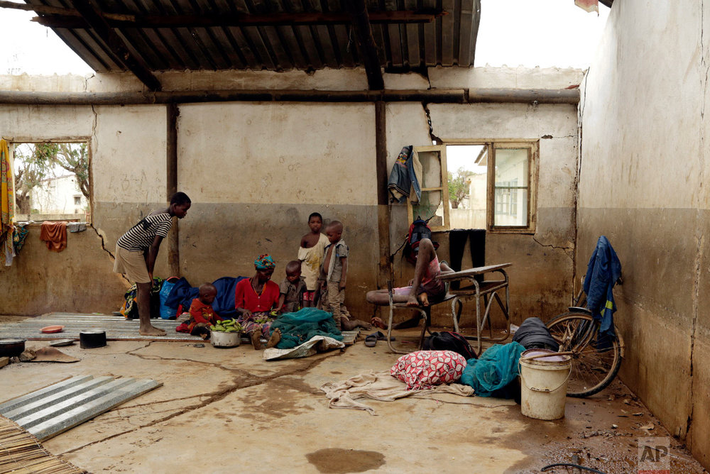 Displaced families rest inside a damaged classroom in Buzi district, 200 kilometers (120 miles) outside Beira, Mozambique, on Saturday, March 23, 2019. (AP Photo/Themba Hadebe)