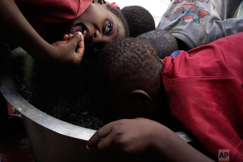 Kids scrape through for remaining rice inside a pot at a displacement centre in Beira, Mozambique, Friday, March 22, 2019. (AP Photo/Themba Hadebe)