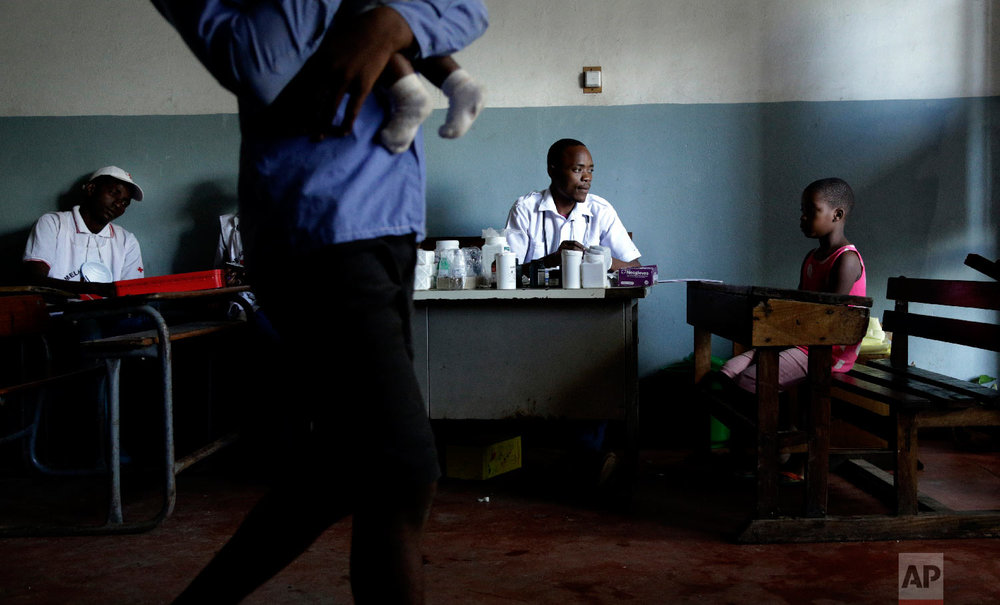 A young girl consults with a doctor at a displacement centre in Beira, Mozambique, Friday, March 22, 2019. (AP Photo/Themba Hadebe)