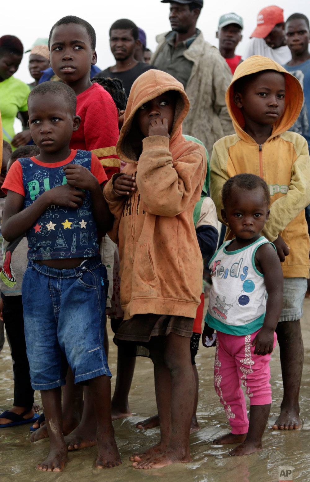 Children wait as their parents disembark from a boat after being rescued from a flooded area of Buzi district, 200 kilometers (120 miles) outside Beira, Mozambique, on Saturday, March 23, 2019. (AP Photo/Themba Hadebe)