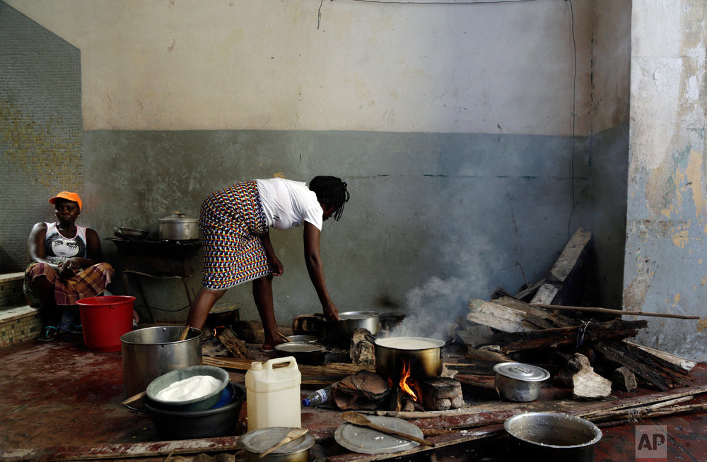 A woman cooks on the floor at a displacement centre in Beira, Mozambique, Friday, March 22, 2019. (AP Photo/Themba Hadebe)