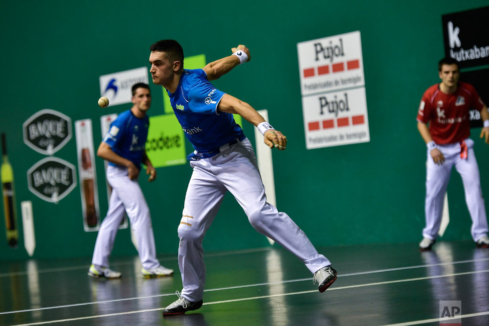 """Basque Ball player or """"pelotari"""" Victor Esteban, returns the ball during a match at Labrit court or fronton, in Pamplona, northern Spain on March 9, 2019. (AP Photo/Alvaro Barrientos)"""