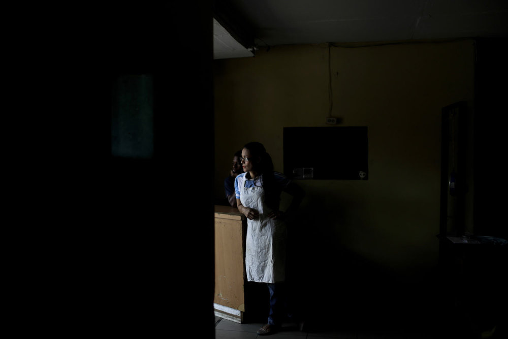 Estela Garcia stands inside the grocery store where she works in Caracas, Venezuela, Tuesday, March 26, 2019. Much of Venezuela remains without electricity as a new power outage spread across the country. (AP Photo/Natacha Pisarenko)