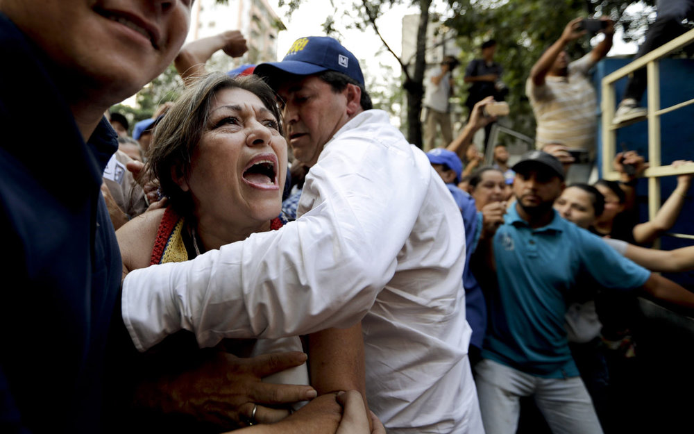 A supporter of Venezuela's self-proclaimed interim president Juan Guaido is stopped as she tries to approach him during a rally in Caracas, Venezuela, on Thursday, March 28, 2019. On Thursday, the Venezuelan government said it has barred Guaido from holding public office for 15 years, though the National Assembly leader brushed off the measure and said it would not derail his campaign to oust President Nicolas Maduro. (AP Photo/Natacha Pisarenko)