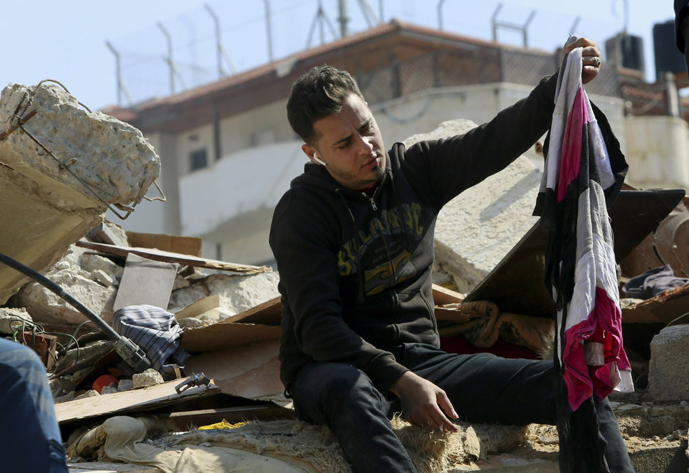 Groom Walid al-Shawa looks at some of his belongings in Gaza City on Wednesday, March 27, 2019, in the rubble of a building that was destroyed in an Israeli airstrike on Monday. Al-Shawa was due to get married in two weeks, but the airstrike destroyed his sister's apartment where he had amassed everything he and his bride needed for the ceremony. (AP Photo/Adel Hana)