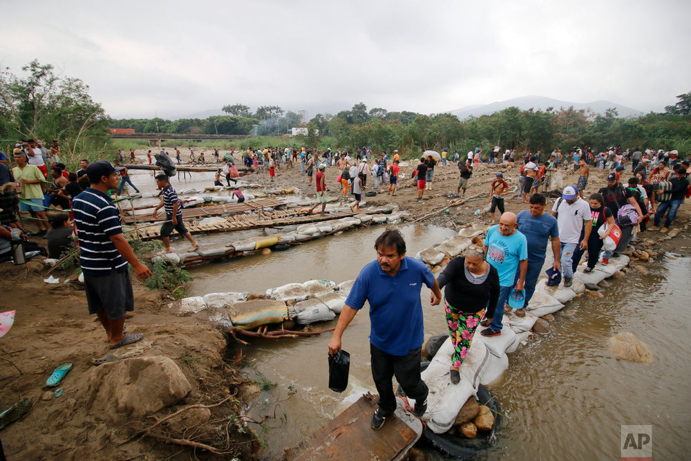 In this March 12, 2019 photo, people cross the Tachira River into Colombia near the Simon Bolivar International bridge, which Venezuelan authorities only open to students and the sick, in Cucuta, Colombia, on the border with Venezuela.  (AP Photo/Schneyder Mendoza)