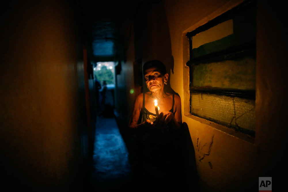 """In this March 14, 2019 photo, 72-year-old Elizabeth Guzman Espitia navigates a narrow passages up to her windowless room she calls her """"little cave"""" during a blackout in the Santa Cruz of the East neighborhood, in Caracas, Venezuela. (AP Photo/Ariana Cubillos)"""