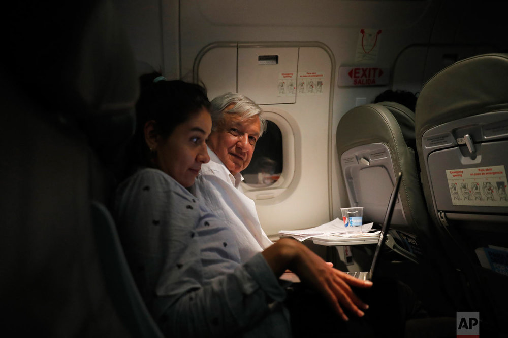 In this March 9, 2019 photo, Mexican President Andres Manuel Lopez Obrador, center, sits with an assistant as he travels in economy class aboard a commercial flight from Guadalajara to Mexico City.  (AP Photo/Marco Ugarte)