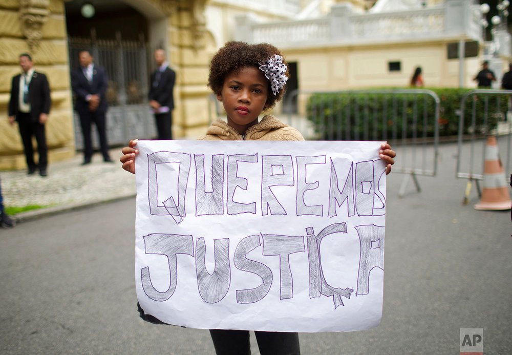 """In this March 20, 2019 photo, a student holds a sign that reads in Portuguese: """"We want justice"""" during a demonstration organized by the NGO Rio de Paz outside the Palacio de Guanabara, the Rio de Janeiro state government office, in Rio de Janeiro, Brazil. (AP Photo/Silvia Izquierdo)"""