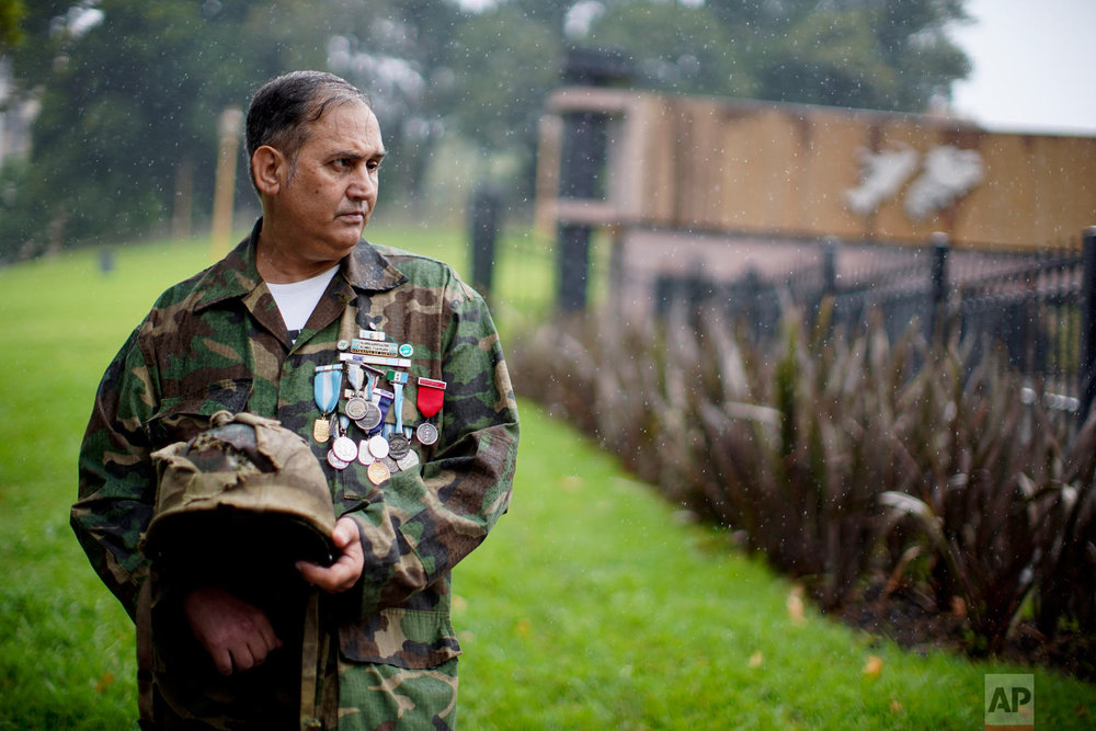 In this March 12, 2019 photo, Argentine war veteran Jorge Altieri poses for a portrait with the blood-stained helmet that saved his life in 1982 during the Falklands war, in Buenos Aires, Argentina. (AP Photo/Natacha Pisarenko)