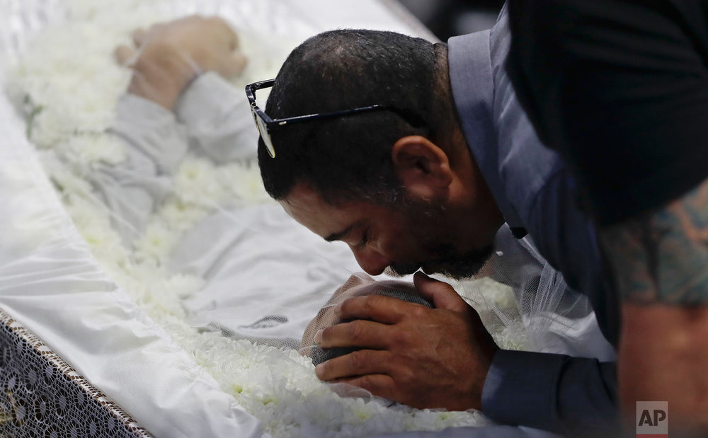 In this March 14, 2019 photo, a relative mourns Caio Oliveira, victim of the shooting at the Raul Brasil State School during a collective wake of the victims in Suzano, greater Sao Paulo area, Brazil. (AP Photo/Andre Penner)