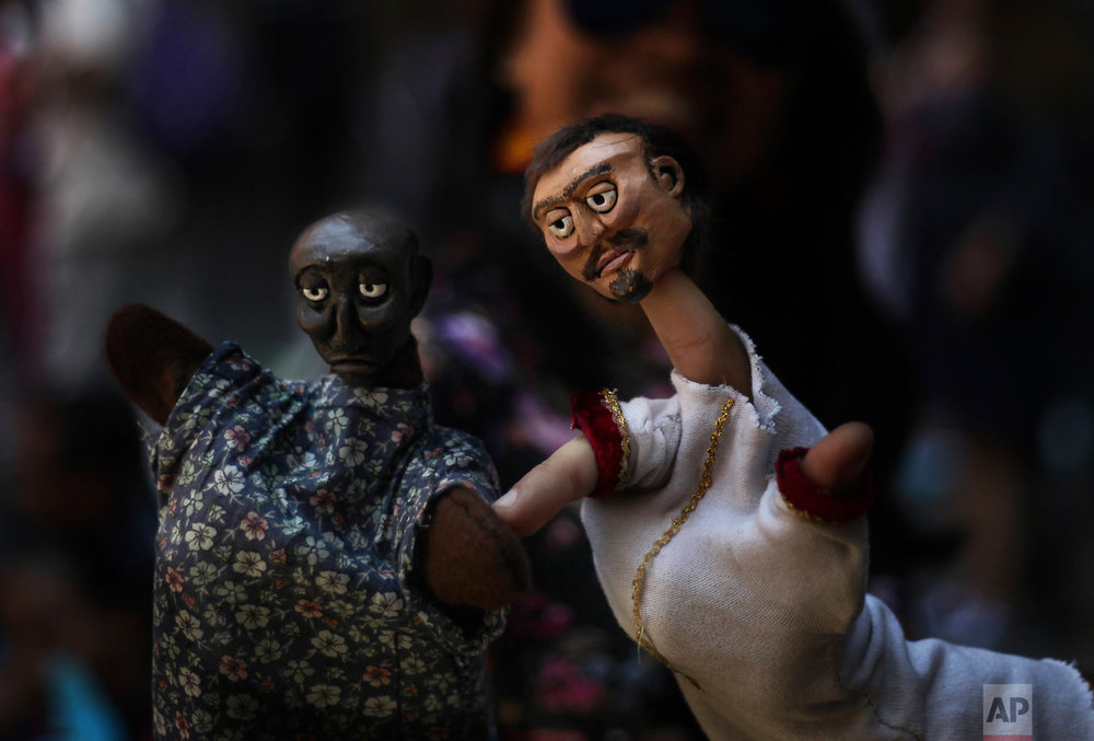 In this March 24, 2019 photo, a puppeteer presents his hand puppets during an event at the National Culture Museum in Mexico City. The event was held in honor of World Puppetry Day, observed earlier in the week on March 21. (AP Photo/Marco Ugarte)