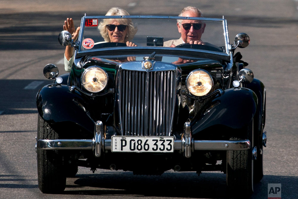 In this March 26, 2019 photo, Prince Charles drives a vintage car with his wife Camilla, Duchess of Cornwall, during a cultural event in Havana, Cuba. The heir to the British throne arrived in Cuba Sunday with an agenda including visits to historic sites, a solar park, organic farm, bio-medical research center, a meeting with entrepreneurs, a cultural gala and a dinner with Cuba's president. (AP Photo/Ramon Espinosa)