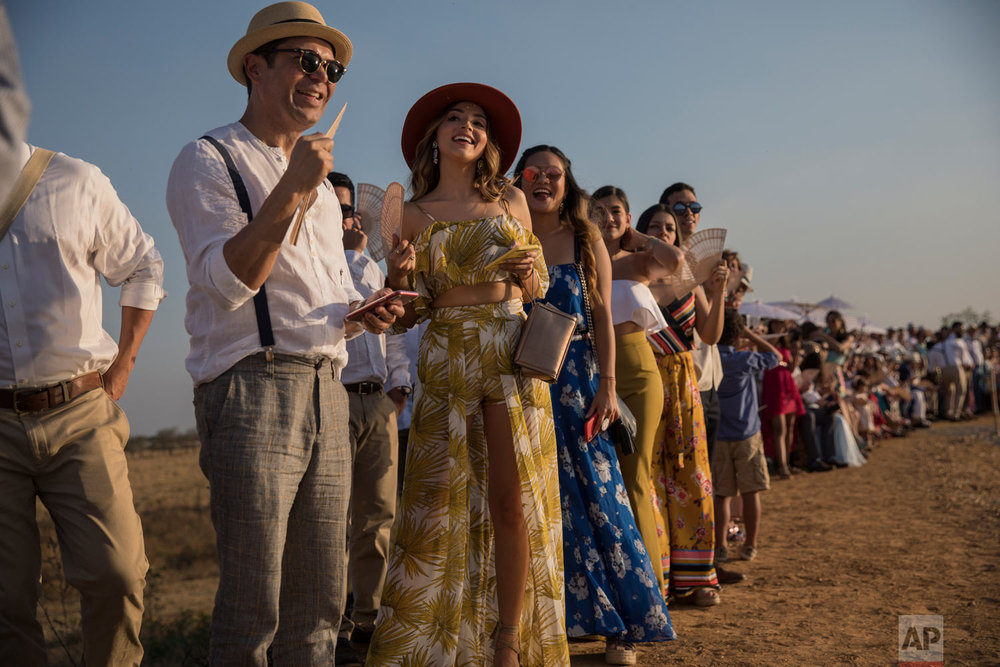 In this Feb. 16, 2019 photo, guests wait for groom Juan Jose Pocaterra and bride Maria Fernanda Vera to arrive to their destination wedding in Acarigua, Venezuela. The wedding guests included wealthy landowners, opposition politicians and a former student leader who nearly lost an eye during an anti-government protest. (AP Photo/Rodrigo Abd)
