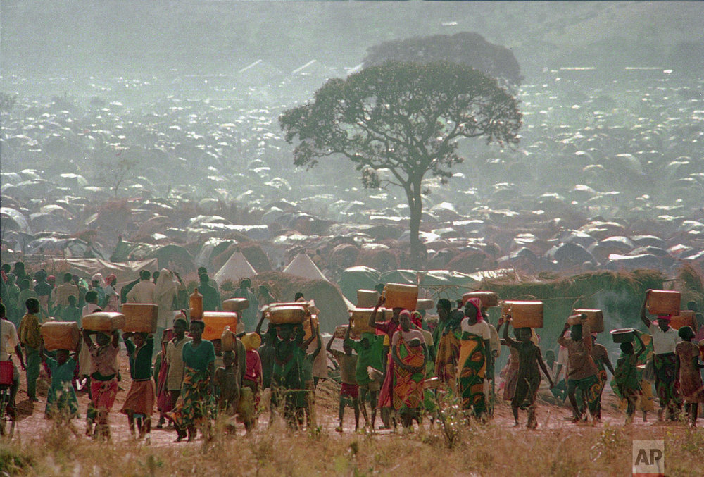 Refugees who fled the ethnic bloodbath in neighboring Rwanda carry water containers back to their huts at the Benaco refugee camp in Tanzania, near the border with Rwanda on May 17, 1994. With a population surpassing 300,000, aid agencies are having difficulty feeding, treating and sheltering them. (AP Photo/Karsten Thielker)