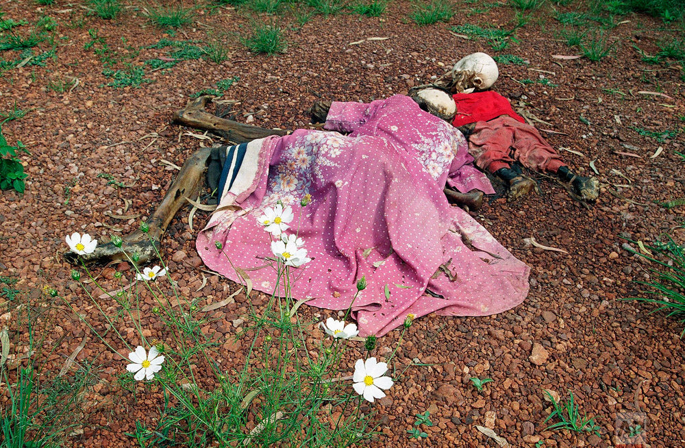 The bodies of a woman and her child lie by a church in Nyarubuye parish, which was the site of an April 14 massacre that survivors say was perpetrated by a militia assisted by government gendarmes, about 95 miles east of the capital Kigali, in Rwanda on May 31, 1994. (AP Photo/Jean-Marc Bouju)