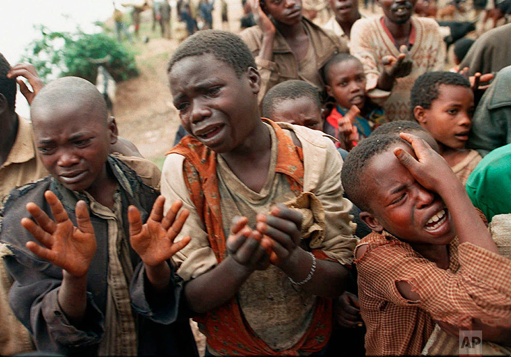 Rwandan refugee children plead with Zairean soldiers to allow them across a bridge separating Rwanda and Zaire where their mothers had crossed moments earlier before the soldiers closed the border, in Zaire, now known as Congo on Aug. 20, 1994. (AP Photo/Jean-Marc Bouju)