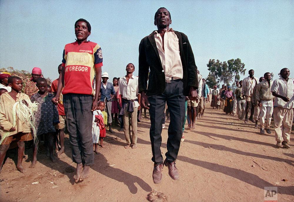 Displaced Hutu civilians in Cyanika, about 50 miles southwest of Kigali, jump in the air as part of government training of new Hutu militias in Rwanda, June 17, 1994. (AP Photo/Jean-Marc Bouju)