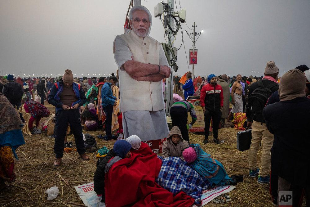 People stand near a poster of Prime Minister Narendra Modi during the Kumbh Mela festival in Allahabad, India, Jan. 14, 2018. (AP Photo/Bernat Armangue)