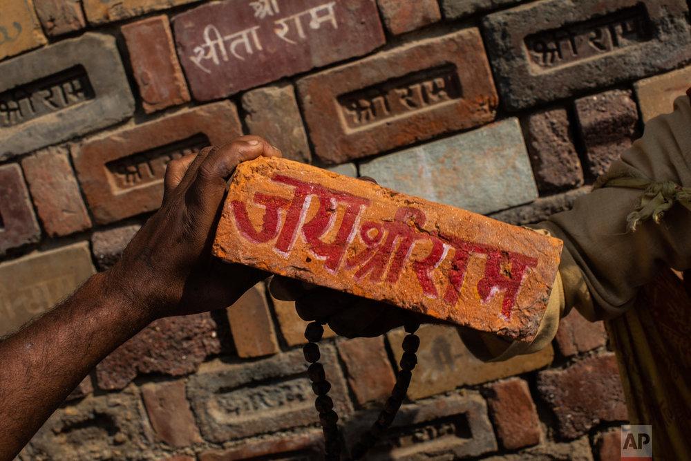 "A man holds a brick reading ""Jai Shree Ram"" (Victory to Lord Ram) as bricks of the old Babri Mosque are piled up in Ayodhya Uttar Pradesh, India, Nov. 25, 2018. (AP Photo/Bernat Armangue)"