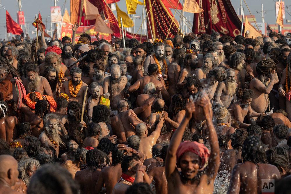 Hindu holy men, take a holy dip at Sangam, the confluence of the rivers Ganges, Yamuna and mythical Saraswati, during the Kumbh Mela festival in Prayagraj, India, Jan. 15, 2019. (AP Photo/Bernat Armangue)