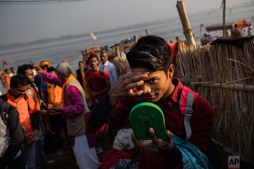 A Hindu hardline supporter applies saffron to his forehead in Ayodhya, Uttar Pradesh, India on Nov. 25, 2018. (AP Photo/Bernat Armangue)