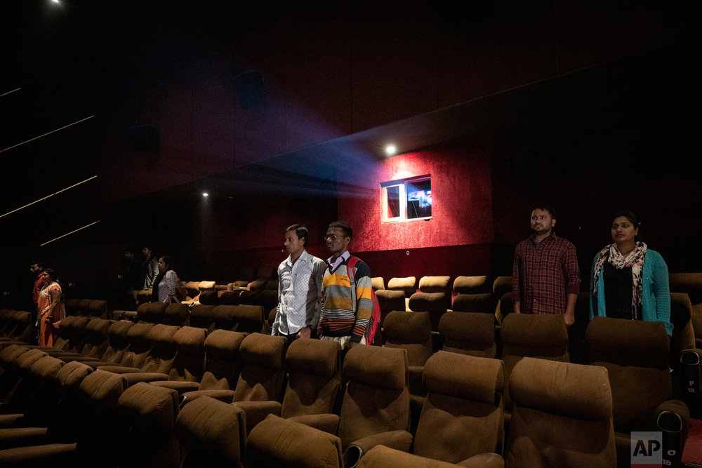 Moviegoers stand as national anthem is played at a cinema before the screening of a movie in Lucknow, Uttar Pradesh, India, Nov. 26, 2018. (AP Photo/Bernat Armangue)